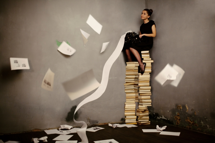 Young woman sitting on the books and typing, toned image
